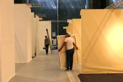 Workers carry crates and tools to their booths to begin installing the artwor...