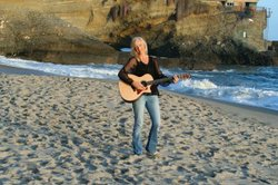 Marlene Hutchinson with her guitar on the beach.