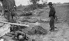 A soldier looking upon a Union soldier's grave with the body of a Confederate soldier seemingly tossed aside in Antietam, Maryland, September 1862.