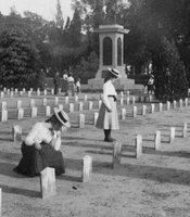 Three women looking at graves in the Confederate Cemetery in Charleston, South Carolina, 1903.