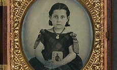 Unidentified girl in mourning dress holding framed photograph of her father as a cavalryman with sword and Hardee hat, 1861.