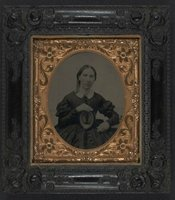 Unidentified woman wearing mourning brooch and displaying framed image of unidentified soldier, 1861.