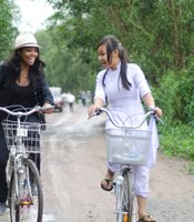 Gabrielle Union and local student Duyen Le ride bikes in Thu Thua, Vietnam.