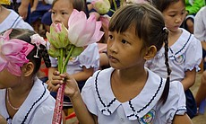 A girl holds flowers during Room to Read's 10 millionth book ceremony in Viet...