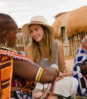Olivia Wilde learning how to make beaded jewelry with women from Umoja Women's Village in Samburu, Kenya.