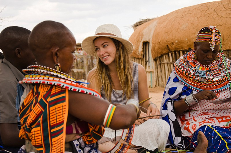 Olivia Wilde learning how to make beaded jewelry with women from Umoja Women'...