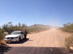 A U.S. Border Patrol agent guards the dirt road that leads to the crime scene...