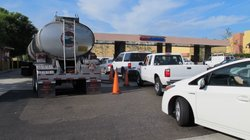 Cars line up at Costco to fill up their tanks with gas.