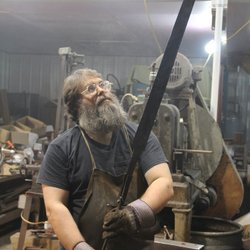 Blacksmith Ric Furrer in his workshop holding his crucible steel Ulfberht bla...