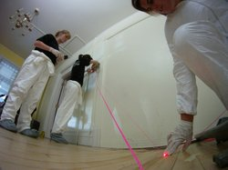 Penn State students connect strings to blood spatter, using a laser pointer in Penn State's crime scene cottage.