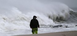 A man stands on the beach as heavy surf from Hurricane Sandy pound the shorel...