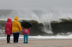 People stand on the beach watching the heavy surf caused by the approaching Hurricane Sandy, on October 28, 2012 in Cape May, New Jersey.