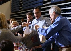 Republican presidential candidate, former Massachusetts Gov. Mitt Romney accepts a food donation from a supporter during a Kettering Storm Relief event on October 30, 2012 in Kettering, Ohio.