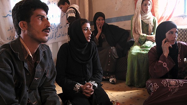 Rafea, Badr and Umm Badr at a village meeting after returning from India.