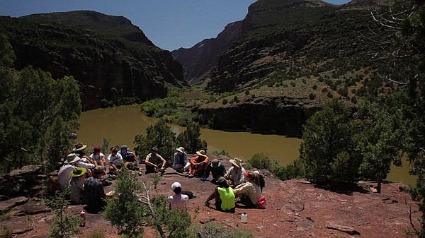 River rafters sit in a circle by the Colorado River.