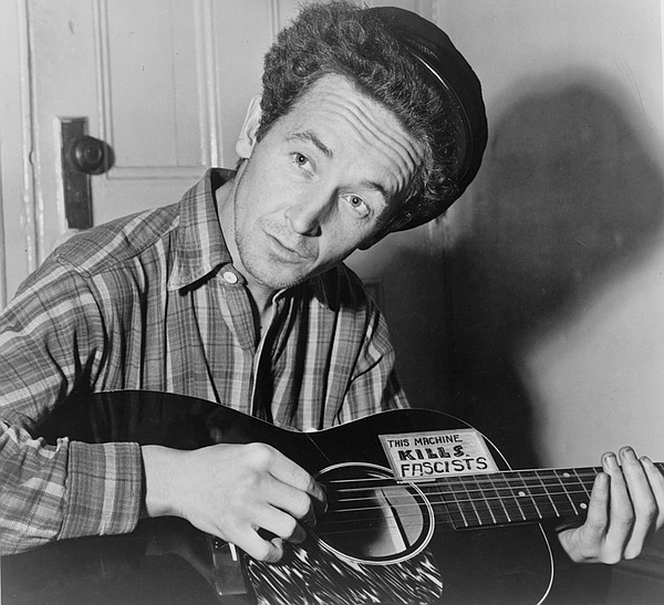 Woody Guthrie with guitar that reads
