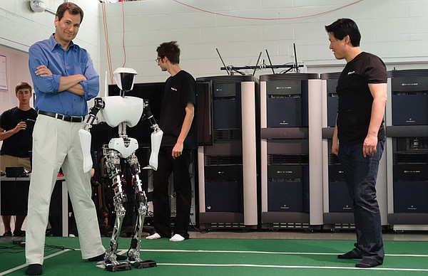 David stands next to CHARLI, a robot built by Dennis Hong...