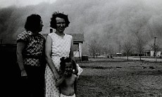 As a black blizzard rolls in to Ulysses, Kansas, two women and a girl pose fo...