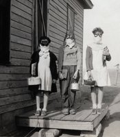 In Lakin, Kansas, three children prepare to leave for school wearing goggles and homemade dust masks to protect them from the dust in 1935.