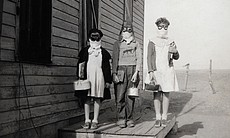 In Lakin, Kansas, three children prepare to leave for school wearing goggles ...