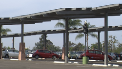 Solar energy canopies in the parking lot of the San Diego Zoo charge cars and...