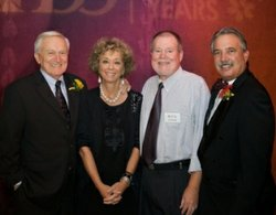 Stephanie Bergsma poses at the KPBS 50th Anniversary Gala with past KPBS General Managers, Paul Steen (left), Doug Myrland (center-right), and current General Manager, Tom Karlo (right).