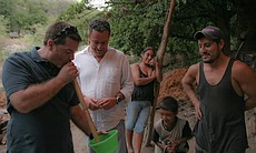Pedro Quintanilla, center, watches his business partner Alejandro Martinez Grey sipping mezcal through a siphon. The mezcalero, or mezcal producer, on the right has just just finished distilling the mezcal.