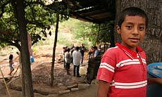 A boy stands beside his family's still in San Luis del Rio, Oaxaca. Behind him, buyers and village producers sample artisanal mezcal.