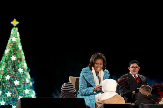 "First Lady Michelle Obama reads ""'Twas the Night Before Christmas"" with Rico Rodriguez to children onstage during the lighting of the National Christmas Tree event on the Ellipse in Washington, D.C., Dec. 6, 2012."