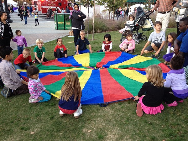 Children circle around the colorful parachute at the City...