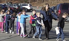 In this photo provided by the Newtown Bee, Connecticut State Police lead children from the Sandy Hook Elementary School in Newtown, Conn., following a shooting there Friday.