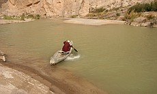 A Mexican citizen paddles his canoe from the northern shoreline of the Rio Grande into Coahuila, Mex. near Boquillas.