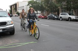 Some cyclists approach a bike trip scanner, embedded in the street on 5th Ave...