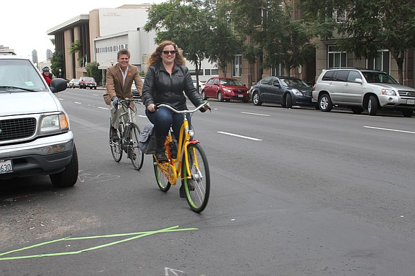 Some cyclists approach a bike trip scanner, embedded in t...