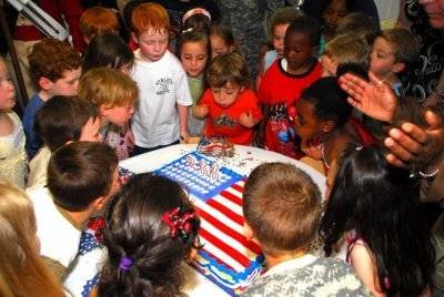 Children at the Child Development Center, blew out the candles on a birthday cake baked for the U.S. Army's 233rd birthday with Secretary of the Army Pete Geren.