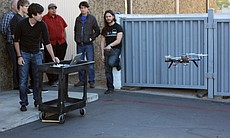 An engineer flies a drone from his computer.