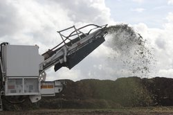 A tree grinder expels ground-up Christmas trees as part of the annual recycli...