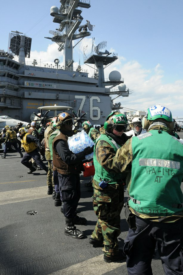 PACIFIC OCEAN (March 19, 2011) Sailors and Marines aboard the aircraft carrier USS Ronald Reagan (CVN 76) load humanitarian assistance supplies onto an HH-60H Sea Hawk helicopter assigned to the Black Knights of Anti-Submarine Squadron (HS) 4.