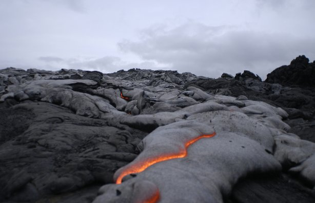 River of lava flowing into the sea, in Kilauea, Hawaii. When the liquid lava solidifies, it continues to build the volcano upwards.