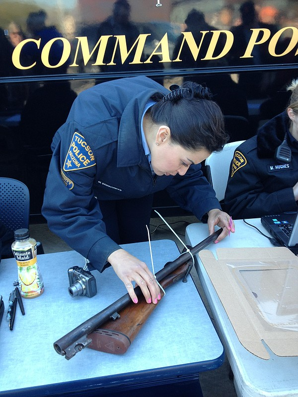 A Tucson police officer inspects a rifle that was brought...