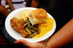 Soul food on a plate including fried chicken, green beans and macaroni & cheese.