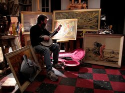 Wayne White playing the banjo in his studio.