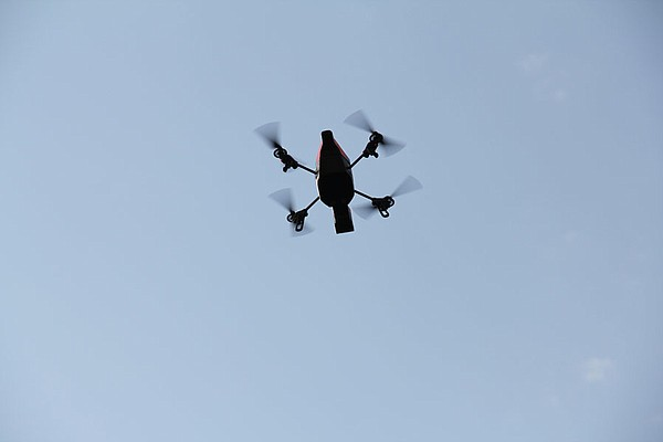 A quadrotor appears in flight.