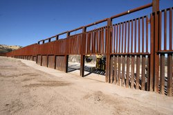 Workers raised the gate on the border fence of the U.S.-Mexico boundary to cl...