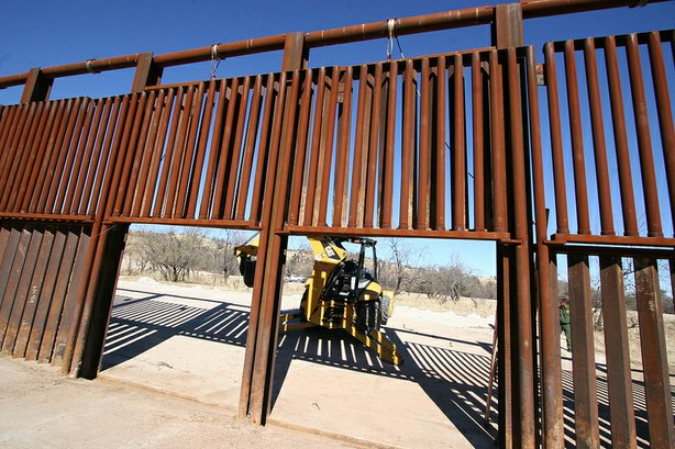 Workers raised the gate on the border fence of the U.S.-Mexico boundary to clean away debris from a cross-border wash. Accumulated debris has knocked down fence segments in the past.