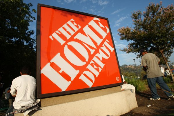 Day laborers wait near a Home Depot home improvement store in hope of finding...