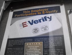 Employers that use E-Verify in the hiring process display a sign in their off...