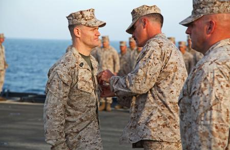 Lieutenant Col. John Wiener, commanding officer, Combat Logistics Battalion 15, 15th Marine Expeditionary Unit, pins the Bronze Star with Combat Distinguishing Device on 1st Sgt. Bradley G. Simmons, Sergeant Major, CLB-15, 15th MEU, during his award ceremony aboard the USS Rushmore, Jan. 25.
