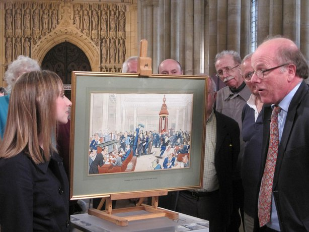 Paintings specialist Dendy Easton examines a Bateman cartoon.