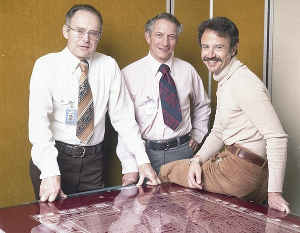 Intel executives Robert Noyce, Gordon Moore, and Andy Grove standing over a m...